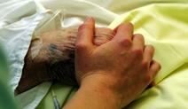 Elderly hand in hospital bed