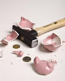 A broken piggy bank with hammer nearby