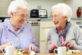 Two older women eating roast dinner with cups of tea, laughing