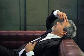 Man holding head on sofa stressed