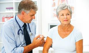 Male GP injecting arm of older woman patient