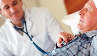 Elderly in man in bed with health worker tending to him