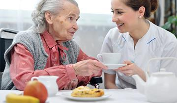 Older woman and younger woman, nurse, smiling at each other
